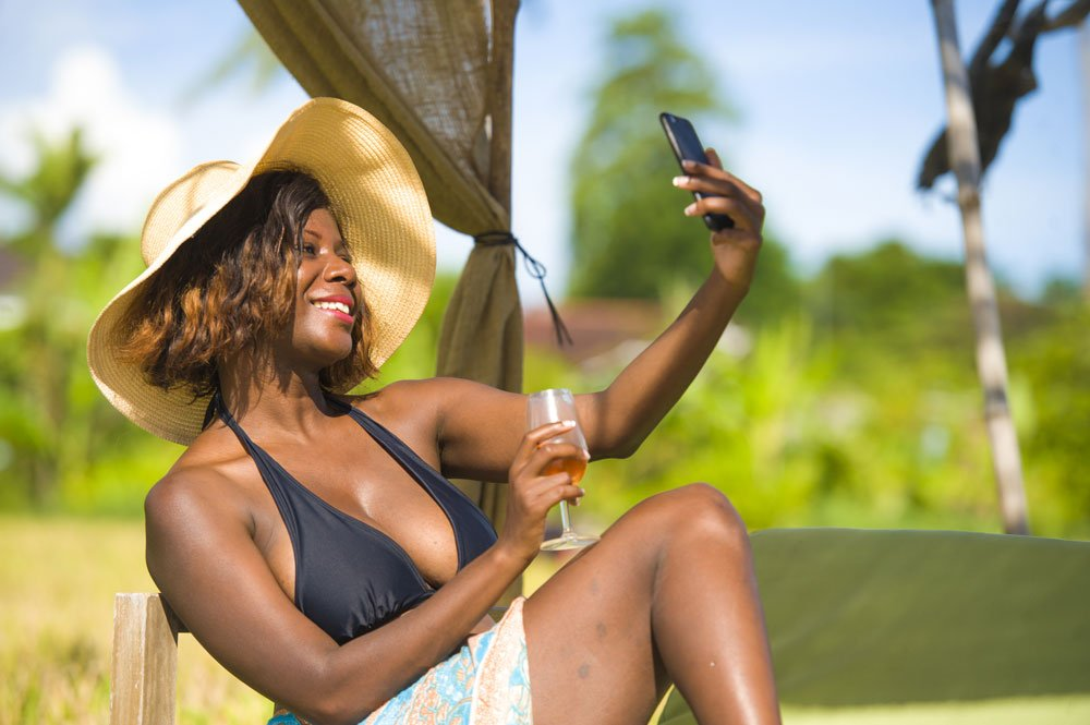 attractive black African American woman in bikini taking selfie picture